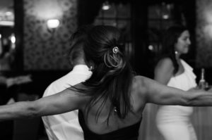 black and white photo from behind the back of a woman dancing with her arms extended out